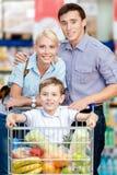 La famiglia conduce il carrello di acquisto con alimento ed il figlio che si siedono là Fotografia Stock