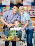 La famiglia conduce il carrello di acquisto con alimento ed il ragazzo che si siedono là Fotografia Stock