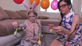 La famiglia decora il salice purulento con le uova di Pasqua archivi video