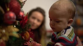La famiglia decora l'albero di Natale La famiglia felice celebra insieme il Natale Movimento lento archivi video
