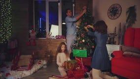 La famiglia decora la casa per il Natale, scena del nuovo anno stock footage
