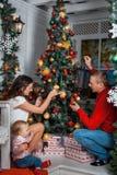 La famiglia decora un albero di Natale Fotografie Stock Libere da Diritti