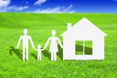 La famiglia di carta con la casa su erba, fa il vostro concetto della casa Immagini Stock Libere da Diritti