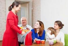 La famiglia di diverse generazioni comunica sopra tè Immagine Stock