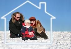 La famiglia di inverno si siede in casa di sogno immagini stock
