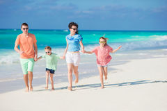 La famiglia di quattro felice su una spiaggia tropicale gode delle vacanze estive Fotografia Stock