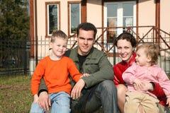 La famiglia di quattro si siede in iarda immagini stock