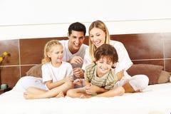 La famiglia di risata sta sedendosi a letto fotografia stock