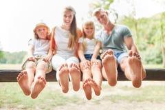 La famiglia ed i bambini stanno sedendo a piedi nudi fotografie stock libere da diritti