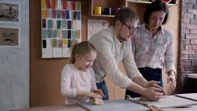 La famiglia felice è corrispondente ed usando il materiale selettivo alla preparazione alle terraglie stock footage