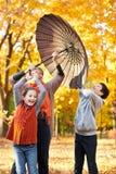 La famiglia felice è nel parco della città di autunno La gente sta posando sotto l'ombrello I bambini ed i genitori stanno sorrid fotografia stock