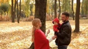 La famiglia felice cammina nel parco in autunno in anticipo archivi video