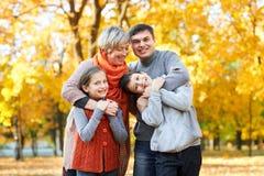 La famiglia felice cammina nel parco della città di autunno Bambini e genitori che posano, sorridenti, giocanti e divertentesi Al immagine stock