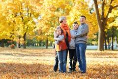 La famiglia felice cammina nel parco della città di autunno Bambini e genitori che posano, sorridenti, giocanti e divertentesi Al fotografia stock