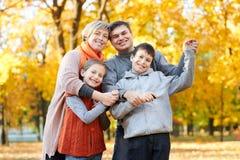 La famiglia felice cammina nel parco della città di autunno Bambini e genitori che posano, sorridenti, giocanti e divertentesi Al fotografia stock libera da diritti
