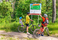 La famiglia felice caucasica con le biciclette è mappa vicina nel parco Fotografie Stock