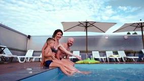La famiglia felice che bagnano nello stagno, la mamma, il papà ed il figlio fanno la spruzzata, la risata, vacanze estive per l'i stock footage