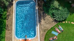 La famiglia felice che si rilassano dalla piscina, la vista aerea del fuco da sopra dei genitori ed i bambini si divertono sulla  fotografie stock libere da diritti