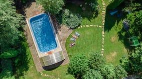 La famiglia felice che si rilassano dalla piscina, la vista aerea del fuco da sopra dei genitori ed i bambini si divertono sulla  immagini stock libere da diritti