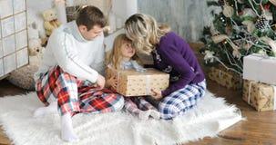 La famiglia felice che si siede al pavimento con il bambino dei regali A di natale gode di un regalo di Natale archivi video