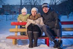 La famiglia felice con il bambino adorabile si siede sul banco Fotografia Stock