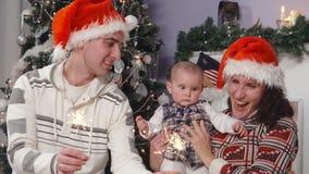 La famiglia felice con il bambino in cappelli del ` s di Santa gode delle luci di Bengala stock footage
