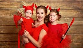 La famiglia felice con il diavolo dei costumi prepara per Halloween immagine stock
