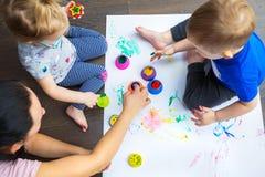 La famiglia felice dei gemelli del bambino e della madre sta dipingendo fotografia stock libera da diritti