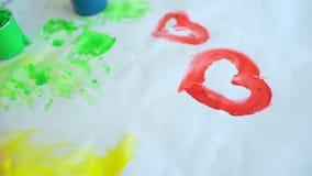 La famiglia felice dipinge i colori Chiuda su di piccole mani sveglie felici del ` s del bambino che rendono a pittura i disegni  stock footage