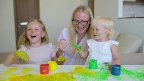 La famiglia felice dipinge i colori La famiglia felice dipinge i colori La madre e la figlia divertendosi e si dipingono ` s sui  stock footage