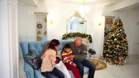 La famiglia felice e allegra nell'umore festivo si diverte insieme e ride, sedendosi sul sofà blu nella stanza decorata festiva video d archivio