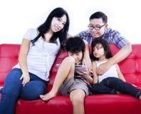 La famiglia felice gode del tempo al sofà rosso - isolato fotografia stock libera da diritti