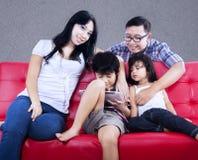 La famiglia felice gode del tempo di qualità sul sofà rosso fotografie stock libere da diritti