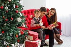 La famiglia felice legge un libro vicino ad un albero di Natale Fotografie Stock Libere da Diritti