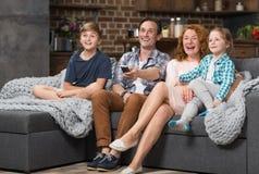 La famiglia felice passa insieme il tempo che si siede sullo strato che guarda la TV, genitori allegri con i bambini Immagini Stock