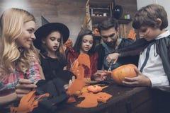 La famiglia felice scolpisce i pipistrelli decorativi da carta per un partito di Halloween Immagine Stock Libera da Diritti