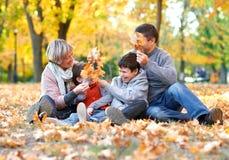 La famiglia felice si siede nel parco della città di autunno sulle foglie cadute Bambini e genitori che posano, sorridenti, gioca fotografie stock libere da diritti