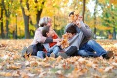 La famiglia felice si siede nel parco della città di autunno sulle foglie cadute Bambini e genitori che posano, sorridenti, gioca immagine stock