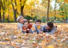 La famiglia felice si trova nel parco della città di autunno sulle foglie cadute Bambini e genitori che posano, sorridenti, gioca fotografia stock libera da diritti