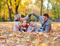 La famiglia felice si trova nel parco della città di autunno sulle foglie cadute Bambini e genitori che posano, sorridenti, gioca immagine stock