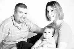 La famiglia felice sorride per la macchina fotografica, in bianco e nero fotografia stock