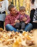 La famiglia felice sta sedendosi nel parco della città di autunno Bambini e genitori Essi che posano, sorridenti, giocanti e dive immagine stock libera da diritti