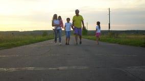 La famiglia felice va lungo la strada in campagna I genitori maturi con tre bambini si divertono sulla natura Famiglia, paternità video d archivio