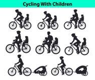 La famiglia, genitori, donna dell'uomo con i loro bambini, ragazzo e ragazza, guidanti bikes Sedili e carrelli sicuri dei bambini Fotografia Stock