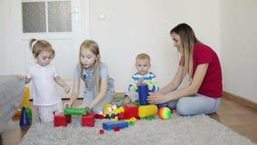 La famiglia gioca con il costruttore sul tappeto a casa archivi video