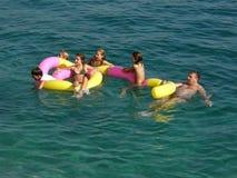 La famiglia gode di nel mare blu Fotografie Stock