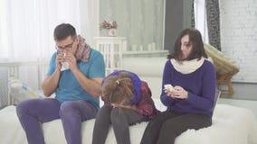 La famiglia ha il raffreddore, papà della mamma e starnuto della figlia che si siedono a casa sul letto video d archivio