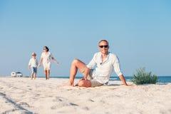 La famiglia ha passato il tempo di vacanza sulla spiaggia abbandonata del mare Immagini Stock