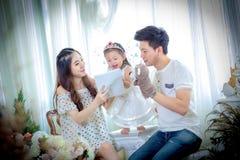 La famiglia, il bambino ed il concetto domestico - genitori sorridenti e poco Fotografia Stock Libera da Diritti