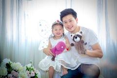 La famiglia, il bambino ed il concetto domestico - genitori sorridenti e poco Fotografia Stock